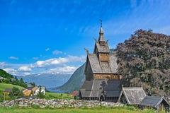 在高山之间的古老木教会 免版税库存照片