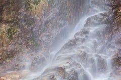 在高山岩石的瀑布 免版税图库摄影