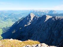 在高山峭壁和谷的看法 在天际,与少量云彩的蓝天的太阳 阿尔卑斯hochries山景 免版税库存图片
