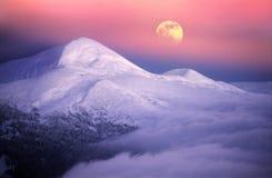 在高山峰顶中的月出 免版税库存图片