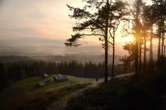 在高山有雾的谷上的日出与小山的老木房子在山森林里 免版税库存照片