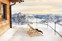在高山瑞士山中的牧人小屋房子的大阳台的Sunbeds山的 库存照片