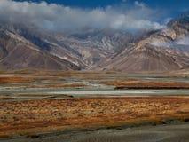 在高山的秋天:在色的峰顶上面覆盖土坎,蓝色河流经在桔子中的谷 图库摄影