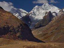 在高山的秋天:巨大的峭壁用冰河雪盖,在前景是与红色草的倾斜,喜马拉雅山 库存照片