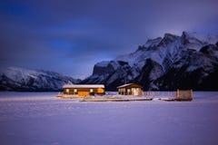 在高山的雪盖的冻湖的空的小船船坞在夜湖Minewanka,班夫国家公园,加拿大期间 免版税库存图片