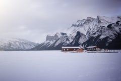 在高山的雪盖的冻湖的空的小船船坞,湖Minewanka,班夫国家公园,加拿大 免版税库存图片