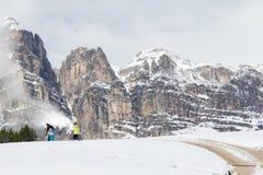 在高山风景的人漫步与沿路的积雪的草甸 免版税库存图片