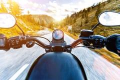 在高山高速公路的摩托车驾驶员骑马,把手视图,奥地利,欧洲 免版税库存照片