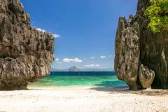 在高岩石之间的海滩 免版税库存照片
