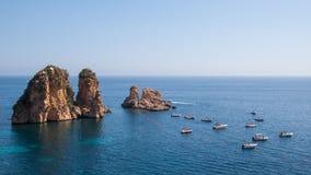 在高峭壁旁边的游船在镇静地中海 库存图片