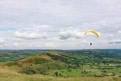 在高峰区的小山的滑翔伞 图库摄影