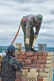 在高房子建筑的瓦工工作 免版税库存图片
