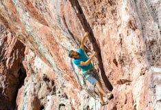 在高橙色自然石墙上的男性攀岩运动员 免版税库存图片