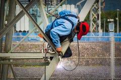 在高电高压杆的焊工工作230 Kv 免版税库存照片
