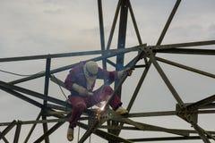 在高电高压杆的焊工工作230 Kv 库存图片