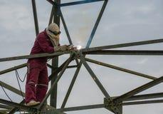 在高电高压杆的焊工工作230 Kv 库存照片