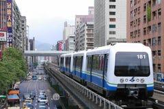 在高的路轨跑的台北地铁火车穿过城市 免版税库存图片