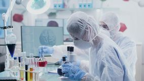 在高端现代研究所两化学家与色的液体样品一起使用 影视素材