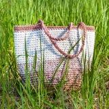 在高绿草,正面图的钩针编织白桃红色站立的袋子 免版税库存图片