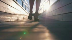 在高跟鞋的女性腿在人行桥走在日落 影视素材