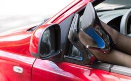 在高跟鞋的妇女腿汽车窗口  免版税库存照片