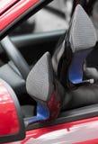 在高跟鞋的妇女腿汽车窗口  免版税图库摄影