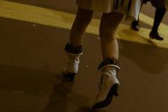 在高跟鞋的年轻和时兴的女性腿在晚上穿上鞋子快速地走在一条拥挤的街上 免版税库存照片