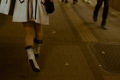 在高跟鞋的年轻和时兴的女性腿在晚上穿上鞋子快速地走在一条拥挤的街上 库存图片