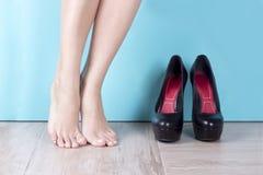 在高跟鞋鞋子附近的光秃的有腿的妇女 锻炼赤脚 亭亭玉立的运动的腿 妇女` s脚和鞋子在硬木地板上 很多 免版税库存图片
