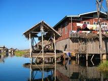 在高跷的木小屋在Inle湖中水域反射了  免版税图库摄影