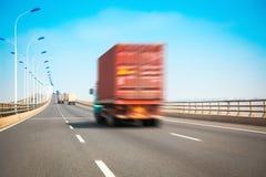 在高速公路桥梁的容器卡车 免版税库存照片