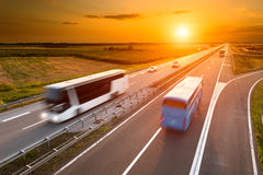 在高速公路的两辆公共汽车在行动迷离 免版税库存照片
