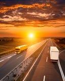 在高速公路的两辆卡车在日落 免版税库存图片
