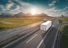 在高速公路的两辆孤立白色卡车在田园诗晴朗的早晨 库存图片