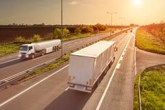 在高速公路的两辆白色卡车在日落 免版税库存图片