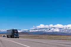 在高速公路的半黑色卡车 免版税图库摄影