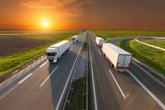在高速公路的四辆白色卡车在田园诗日落 免版税库存照片