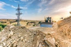 在高速公路的建筑工作的挖掘机移动的地球 免版税图库摄影
