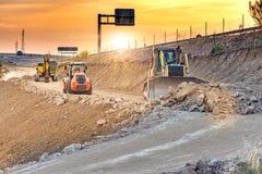 在高速公路的建筑工作的挖掘机移动的地球 免版税库存图片