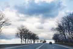 在高速公路的灰色多雨云彩在早期的春天 免版税库存照片