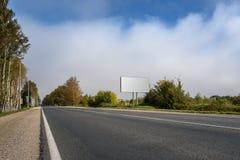 在高速公路的空白的广告牌和天空背景与云彩的 库存照片