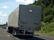 在高速公路的篷布隐蔽的半卡车 库存图片
