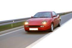 在高速公路的红色快速赛车 库存照片