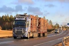 在高速公路的蓝色富豪集团FH16木运输卡车在冬天 免版税库存照片