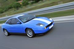 在高速公路的蓝色快速赛车 库存图片
