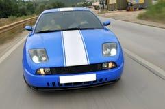 在高速公路的蓝色快速跑车 库存图片