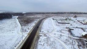 在高速公路的黑汽车乘驾在降雪 在长向右转的乘驾对冬天森林鸟瞰图 股票录像