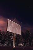 在高速公路附近的空白的广告牌在冬天晚上 免版税库存照片