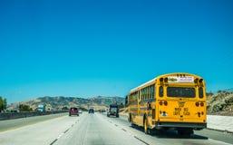 在高速城市间的高速公路的黄色校车在洛杉矶附近 免版税库存照片