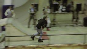 在高速的四轮溜冰者乘驾 摄影师 在skatepark的极端竞争 坚硬特技 股票录像